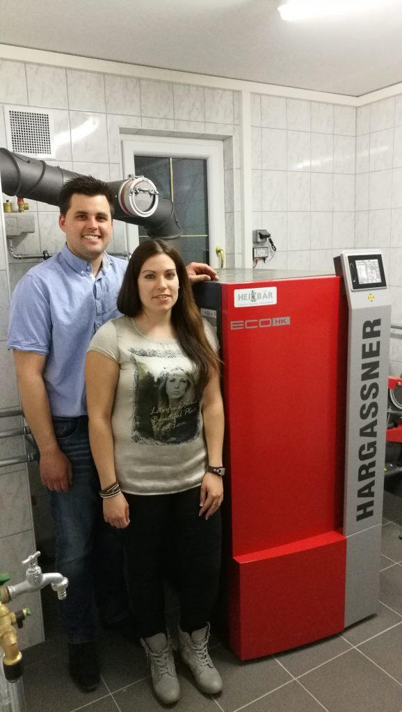 Hier steht Familie Gruber vor Ihrer neuen Hackschnitzelheizung von Hargassner. Ausgeführt von Installateur Heizbaer.