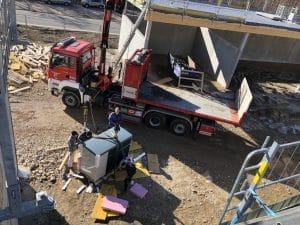 Feuerwehrkran Alland hebt Hoval Luftärmepumpe mit Heizbär Mitarbeitern aus das Bauhof Dach