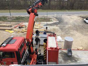 Feuerwehrkran Alland hebt Hoval Luftärmepumpe von Heizbär auf Feuerwehrdach